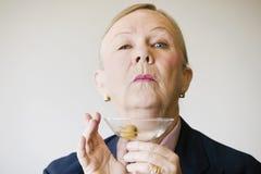 Mujer mayor dramática con un Martini imagenes de archivo