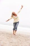 Mujer mayor el el día de fiesta que se ejecuta a lo largo de la playa del invierno foto de archivo