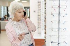 Mujer mayor elegante en tienda óptica Imagen de archivo libre de regalías