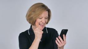 Mujer mayor emocionada para el éxito mientras que usa Smartphone almacen de video