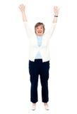Mujer mayor emocionada que presenta con los brazos levantados Imagen de archivo libre de regalías