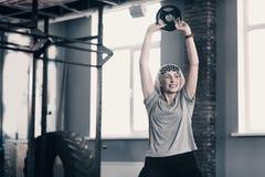Mujer mayor enérgica que levanta encima de un disco del peso Imagen de archivo