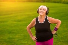 Mujer mayor en auriculares Imagen de archivo libre de regalías