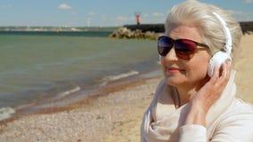 Mujer mayor en auriculares con smartphone en la playa almacen de video