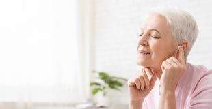 Mujer mayor en auriculares que escucha el audiolibro foto de archivo