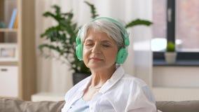 Mujer mayor en auriculares que escucha la música almacen de metraje de vídeo