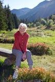 Mujer mayor en banco por el lago en montañas fotografía de archivo