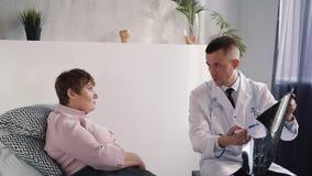 Mujer mayor en blusa rosada que consulta con el doctor inteligente profesional en clínica médica almacen de metraje de vídeo