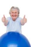 Mujer mayor en bola del ejercicio con los pulgares para arriba Foto de archivo libre de regalías