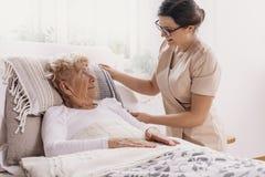Mujer mayor en cama de hospital con el asistente social imagenes de archivo