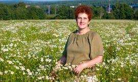Mujer mayor en campo de la manzanilla en pueblo Fotografía de archivo libre de regalías