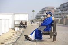 Mujer mayor en capa y sombrero azules en un banco Fotografía de archivo libre de regalías