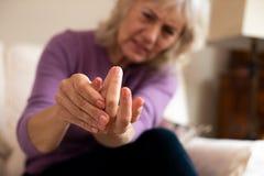 Mujer mayor en casa en el sufrimiento del dolor con artritis foto de archivo libre de regalías