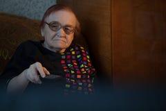 Mujer mayor en casa que mira la TV y el cambio Foto de archivo