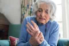 Mujer mayor en casa que sufre con artritis foto de archivo libre de regalías