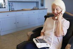 Mujer mayor en casa usando el teléfono con llaves clasificadas excesivas imagenes de archivo