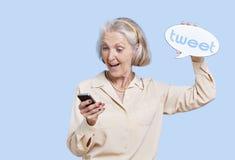 Mujer mayor en casual usando medios sociales en su Smartphone contra fondo azul imagenes de archivo