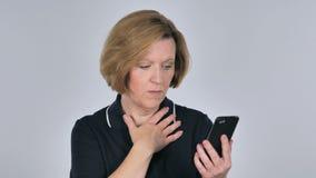 Mujer mayor en choque mientras que usando Smartphone almacen de video