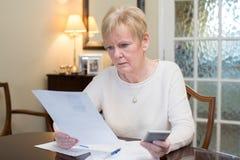 Mujer mayor en cuestión que revisa finanzas nacionales fotos de archivo
