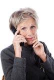 Mujer mayor en cuestión que usa un teléfono Foto de archivo