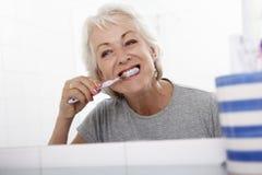 Mujer mayor en dientes de cepillado del cuarto de baño fotografía de archivo libre de regalías