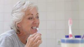 Mujer mayor en dientes de cepillado del cuarto de baño metrajes
