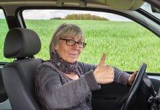 Mujer mayor en el coche con los pulgares para arriba Fotos de archivo libres de regalías