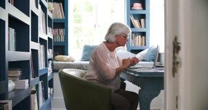 Mujer mayor en el escritorio que trabaja en Ministerio del Interior con el ordenador portátil almacen de metraje de vídeo