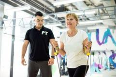 Mujer mayor en el gimnasio, entrenamiento del susspension Imagenes de archivo