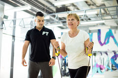 Mujer mayor en el gimnasio, entrenamiento del susspension Fotografía de archivo libre de regalías