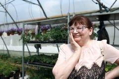 Mujer mayor en el invernadero de flores Imagen de archivo libre de regalías