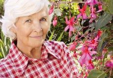 Mujer mayor en el jardín Fotos de archivo libres de regalías