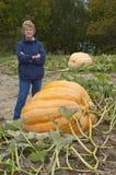 Mujer mayor en el jardín que produce la calabaza gigante Imágenes de archivo libres de regalías