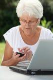 Mujer mayor en el país con el ordenador imagen de archivo