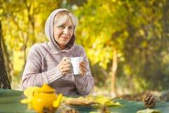 Mujer mayor en el suéter que sostiene una taza de té Foto de archivo