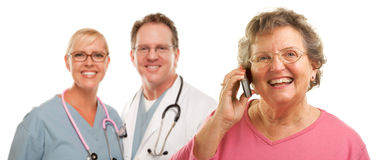 Mujer mayor en el teléfono celular y los doctores Behind Foto de archivo libre de regalías