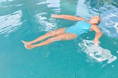 Mujer mayor en ella detrás en el agua durante yoga de la aguamarina foto de archivo