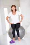 Mujer mayor en gimnasia en una bola de la gimnasia Imagenes de archivo