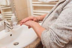 Mujer mayor en la albornoz que aplica la crema de la mano en el cuarto de baño, primer imagen de archivo