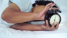 Mujer mayor en la cama que presiona el botón de la cabezada en el despertador de la mañana almacen de video