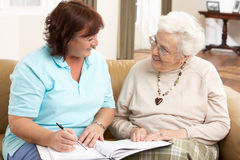 Mujer mayor en la discusión con el visitante de la salud Imagen de archivo libre de regalías