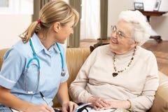 Mujer mayor en la discusión con el visitante de la salud Fotografía de archivo libre de regalías