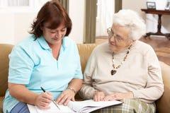 Mujer mayor en la discusión con el visitante de la salud Foto de archivo
