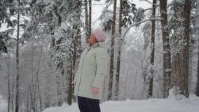 Mujer mayor en la ropa caliente que se coloca en el medio de bosque nevado y que admira el paisaje hermoso útil almacen de metraje de vídeo