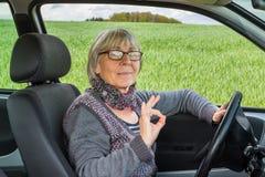 Mujer mayor en las demostraciones de coche todo perfecto Imagen de archivo