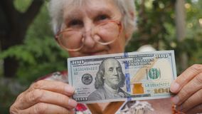 Mujer mayor en las lentes que muestran cientos billetes de dólar en cámara y la sonrisa al aire libre Abuelita que sostiene efect almacen de metraje de vídeo