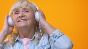 Mujer mayor en los auriculares blancos que escucha la música, disfrutando de melodía preferida metrajes