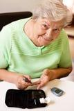 Mujer mayor en medida del azúcar de sangre fotos de archivo