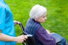 Mujer mayor en silla de ruedas con la enfermera Fotos de archivo libres de regalías