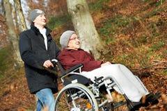 Mujer mayor en silla de ruedas e hijo en el parque Fotografía de archivo libre de regalías